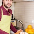 Smiling young man with apron holding a rolling pin — Stock Photo #40002907