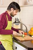 Yakışıklı delikanlı mutfak kesme sebze — Stok fotoğraf