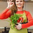 Beautiful happy young woman with apron holdin a pot and making o — Stock Photo