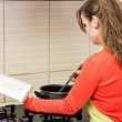 Beautiful young woman reading a cookbook , looking for recipe, w — Stock Photo #44152965