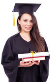 Beautiful woman student in graduation gown holding book and  dip — Stock Photo