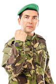 Serious young soldier with arm raised showing his fist — Stock Photo