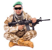 Young soldier with a gun sitting cross legged — Stock Photo