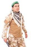Young soldier with green beret and arabian scarf looking at came — Stock Photo