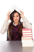 Studio shot of unhappy student with book on the head sitting at  — Stockfoto