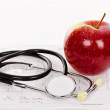 Red apple and stethoscope on an electrocardiogram (ECG) chart — Stock Photo