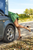 Woman standing near her broken car and looking to the engine — Stock Photo