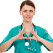 Attractive female doctor with stethoscope making heart shape — Stock Photo #51332183