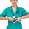 Attractive female doctor with stethoscope making heart shape — Stock Photo #51332339