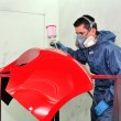 Worker painting a red car bumper. - Stock Photo