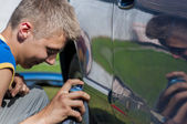 Boy spraying a car. — Stock Photo