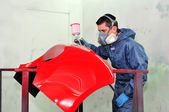 Worker painting a red car bumper. — Stock Photo