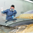 Stock Photo: Worker painting car.