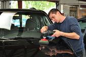 Worker polishing a car bonnet. — Stock Photo