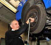 Mechanic repairing a car wheel — Stock Photo