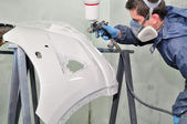 Worker painting a car bumper. — Stock Photo