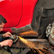 Stock Photo: Mgrinding welded car body.