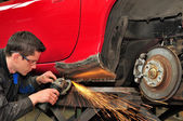 Man grinding welded car body. — Stock Photo