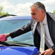 Man wearing suit cleaning a car. — Stock Photo
