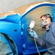 Stock Photo: Worker painting blue car.