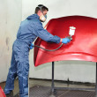 Stock Photo: Worker painting a red bonnet.