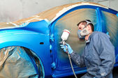 Worker painting blue car. — Stock Photo