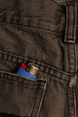 Black blue jeans with lighter in the back pocket — Stock Photo