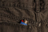 Black denim jeans with a lighter in the back pocket — Stock Photo