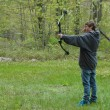 Stock Photo: Teenage boy shooting compound bow with arrow in the scene
