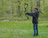 Teenage boy shooting compound bow with arrow in the scene — Stock Photo