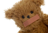 Stuffed teddy bear with bandaid on mouth — Stock Photo