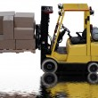 Industrial forklift loaded with boxes with water puddle reflection - Stock Photo