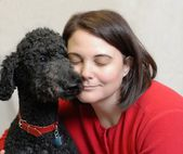 Touching moment between woman and standard poodle dog — ストック写真