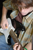Fourteen year old teenage boy playing or practicing guitar — Stock Photo