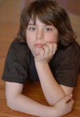Twelve year old boy with chin resting in hands and pensive expression on face — Stock Photo