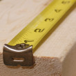 Measuring tape lined up ready to measure piece of wood - 
