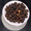 Whole peppercorns in white dispenser on black background - Stock Photo