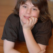 Good looking young boy age 12 with chin resting in hands — Stock Photo #24323589