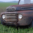 Rusty old pick up truck in rural field - Stock Photo