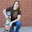 Teenage boy with skateboard displaying attitude of skateboarding culture — Stock Photo