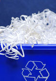 Blue recycle bin with shredded paper spilling out — Stock Photo