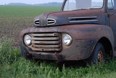 Rusty old pick up truck in rural field — Stock Photo