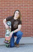 Teenage boy with skateboard displaying attitude of skateboarding culture — Stock Photo