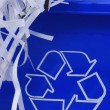 Shredded paper spilling out of blue recycle bin — Stock Photo #24363103