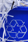 Shredded paper spilling out of blue recycle bin — Stock Photo