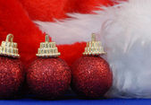 Details on santa hat and red christmas ornaments — Stock Photo