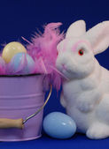 Easter bunny with easter eggs on blue background — Stock Photo