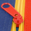 Red zipper on blue and yellow canvas — Stock Photo #24374389