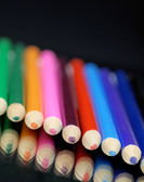 Bright colorful pencil crayons with reflection — Stock Photo