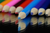 Blue pencil crayon sticking out among several other bright pencil crayons — Stock Photo